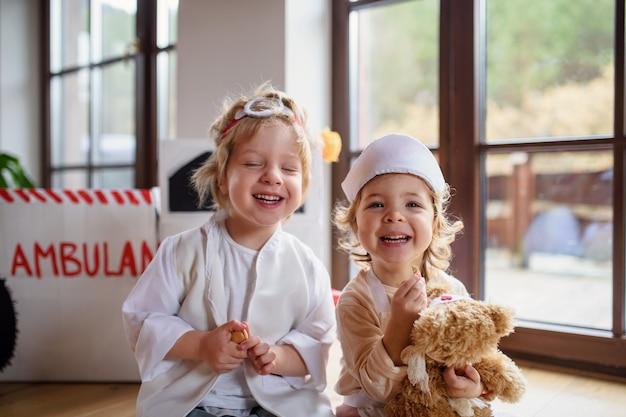 Duas crianças pequenas com uniformes de médico dentro de casa, brincando e se divertindo.