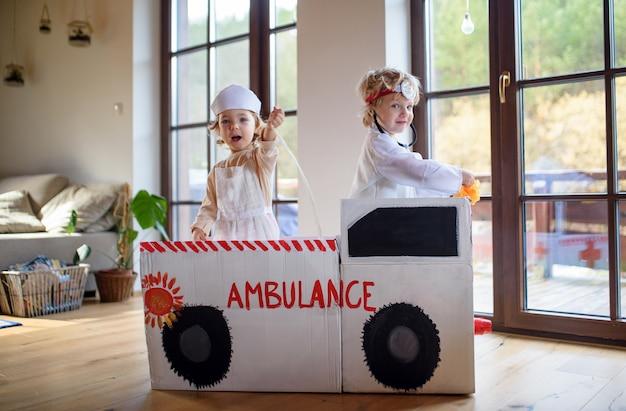 Duas crianças pequenas com uniformes de médico e uma ambulância de brinquedo dentro de casa, brincando.
