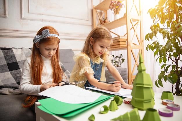 Duas crianças pequenas, meninas juntas na criatividade da casa, crianças felizes fazem brinquedos feitos à mão para