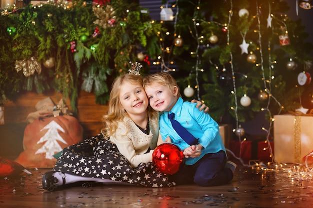 Duas crianças pequenas perto com uma árvore de natal