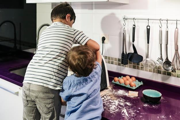 Duas crianças preparando panquecas com um robô de cozinha.