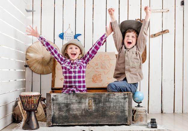 Duas crianças rindo com as mãos para cima