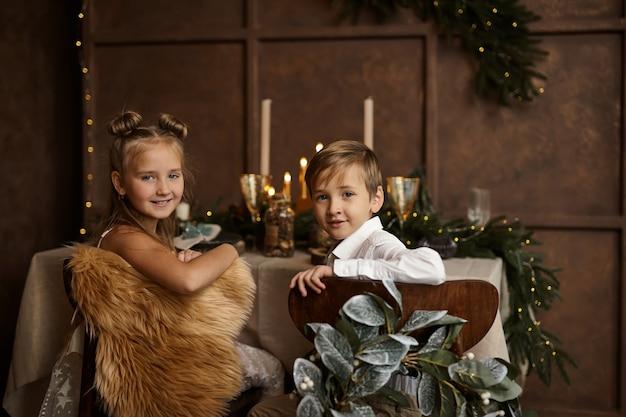 Duas crianças sentadas em cadeiras perto de uma mesa festiva