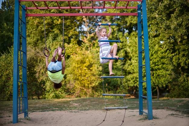 Duas crianças sorridentes felizes estão exercitando em um campo de esportes.