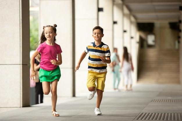 Duas crianças sorridentes, menino e menina correndo juntos na cidade, no dia de verão