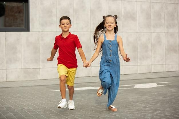 Duas crianças sorridentes, menino e menina, correndo juntos na cidade no dia de verão