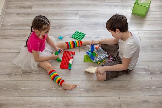 Duas crianças, um menino e uma menina, sentam-se no chão da sala e brincam em construções de plástico. vista do topo