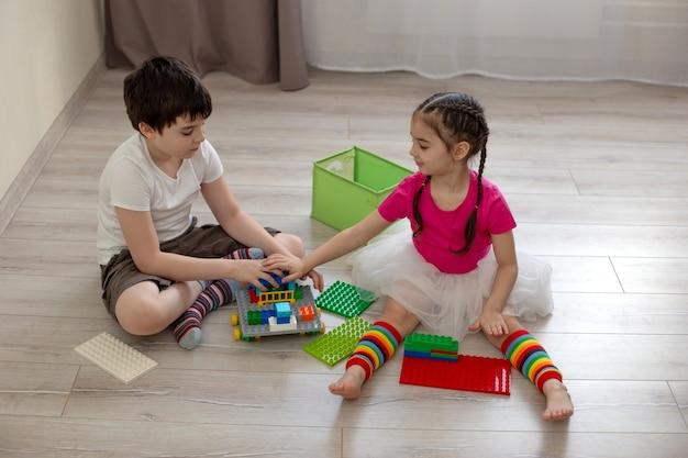 Duas crianças, um menino e uma menina, sentam-se no chão e brincam em construções de plástico