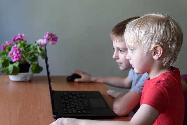 Duas crianças usam um laptop