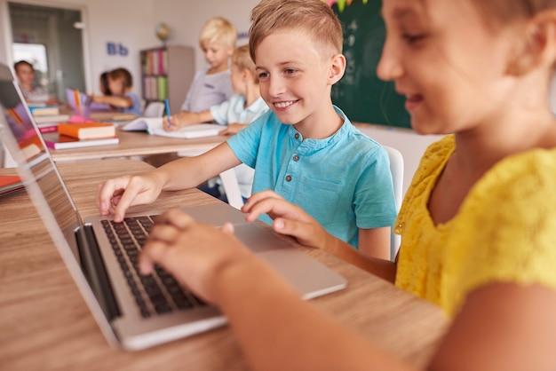 Duas crianças usando laptop durante a aula