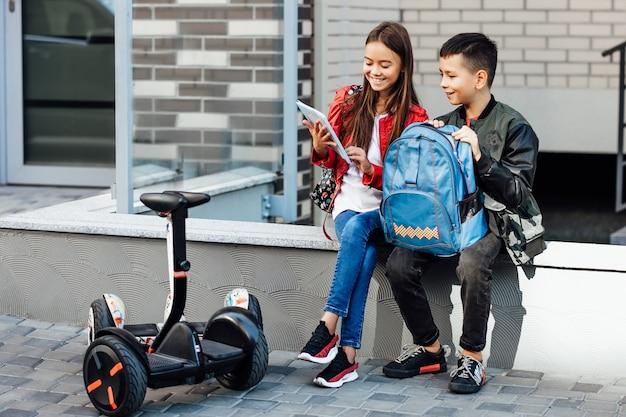 Duas crianças vão para a escola para giroscooters