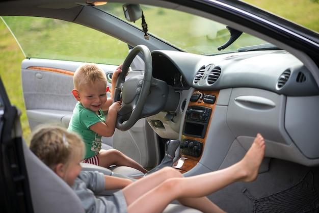Duas criancinhas fofas - um irmão e uma irmã brincando de dirigir o carro ao volante.