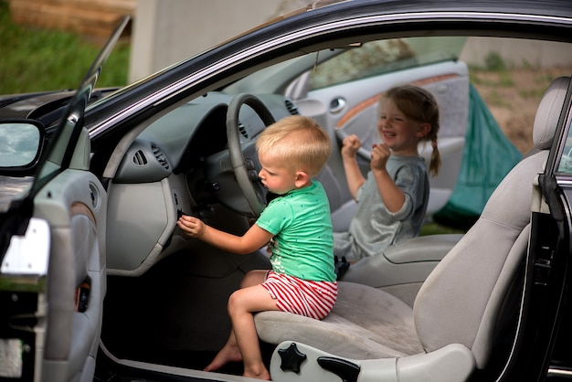 Duas criancinhas fofas - um irmão e uma irmã brincando no carro ao volante.