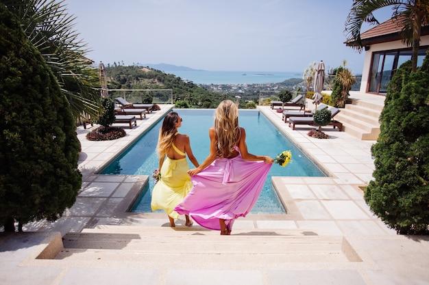 Duas damas de honra em vestidos coloridos brilhantes amarelo e rosa à beira da piscina com buquês com uma maravilhosa vista tropical do mar na villa