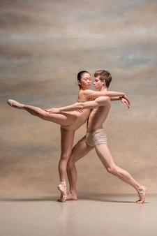Duas dançarinas de balé posando sobre cinza
