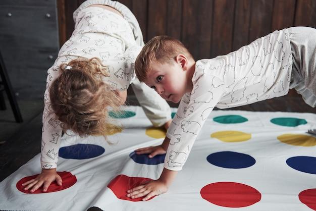Duas de crianças felizes brincando no twister em casa. irmão e irmã se divertem no feriado