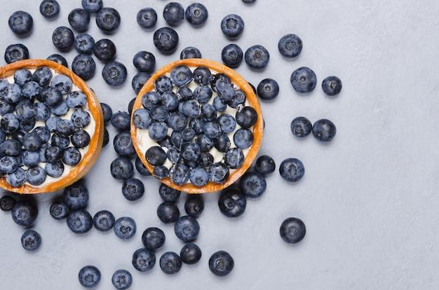 Duas deliciosas sobremesas de mini torta de mirtilo com frutas frescas. cozinha francesa. cama plana, close-up