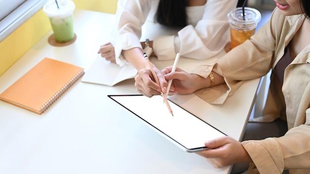 Duas designer feminino trabalhando em um novo projeto com tablet digital no escritório.