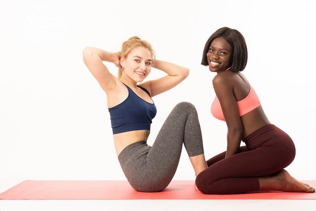 Duas desportistas musculares internacionais fazendo exercícios de par. meninas realizando abdominais e flexões