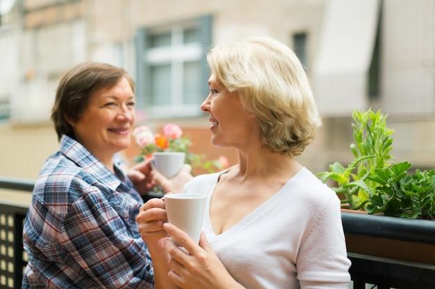 Duas donas de casa maduras bebendo chá no terraço