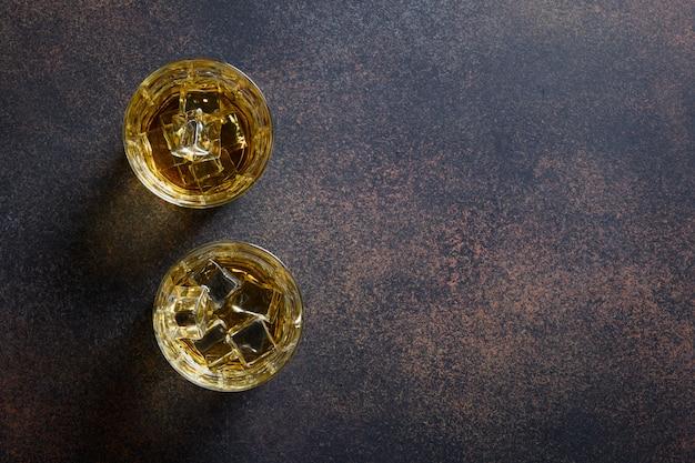 Duas doses de whisky com cubo de gelo na mesa marrom escura.