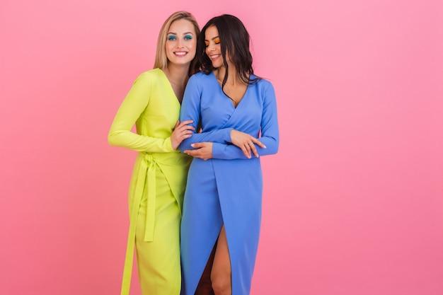 Duas elegantes amigas atraentes e sorridentes posando na parede rosa em elegantes vestidos coloridos de cor azul e amarelo, tendência da moda de primavera