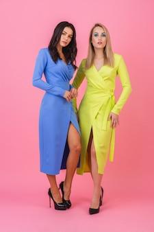Duas elegantes mulheres atraentes e sexy posando de altura total na parede rosa em elegantes vestidos coloridos de cor azul e amarelo, tendência da moda de primavera