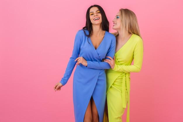 Duas elegantes mulheres atraentes e sorridentes com vestidos coloridos se divertindo posando na parede rosa, roupas de cor azul e amarela, tendência da moda de verão