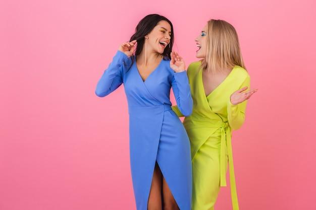 Duas elegantes mulheres atraentes e sorridentes se divertindo posando na parede rosa em elegantes vestidos coloridos de cor azul e amarelo, tendência da moda primavera