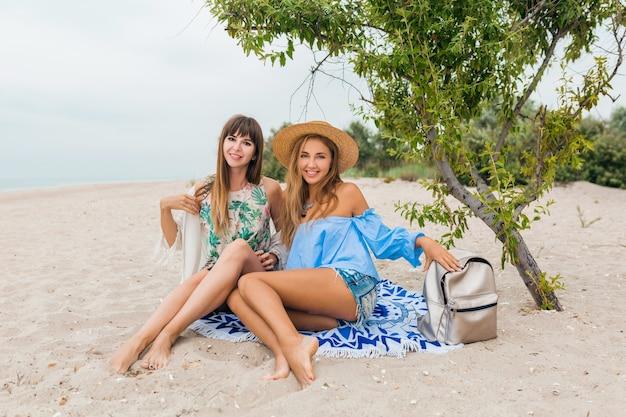 Duas elegantes mulheres muito sorridentes sentadas na areia nas férias de verão em uma praia tropical, amigos viajam juntos