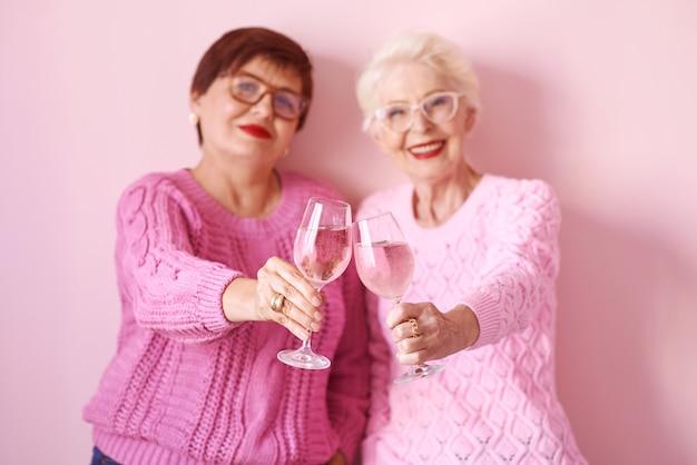 Duas elegantes mulheres sêniors em suéteres rosa e taças de vinho rosa em fundo rosa