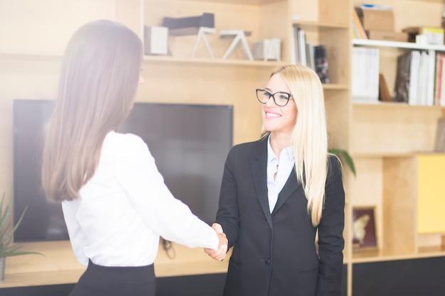 Duas empresárias apertando as mãos enquanto fecham um acordo ou parceria