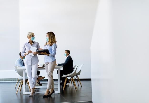 Duas empresárias, maduras e jovens, conversando no escritório e usando máscara como proteção contra vírus