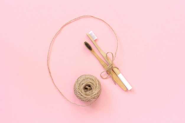 Duas escovas de bambu natural eco-friendly com cerdas brancas e pretas, amarradas com barbante em fundo rosa