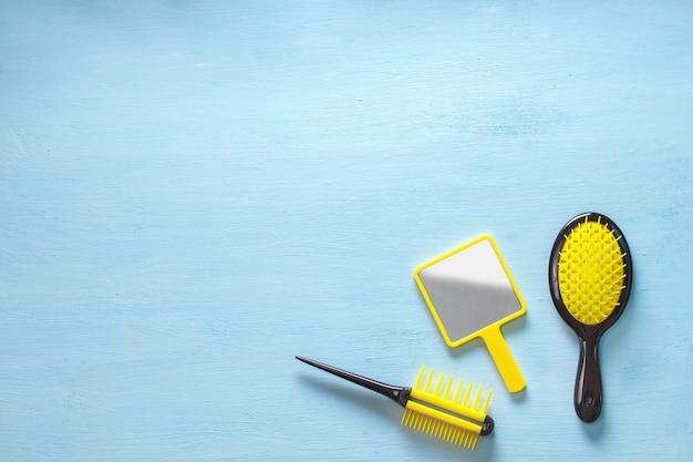 Duas escovas de crista de pente de cabelo amarelo com alça para todos os tipos e espelho isolado no espaço azul da cópia. configuração minimalista feminina plana
