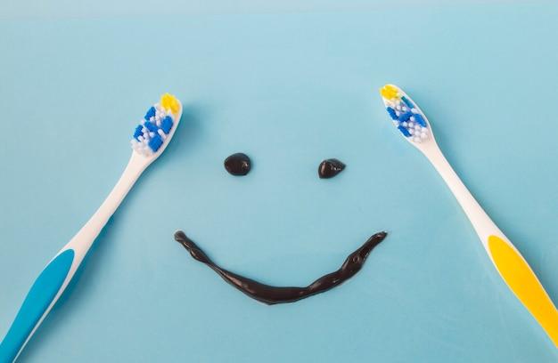 Duas escovas de dente coloridas de plástico e um tubo de sorriso engraçado de uma pasta de dente preta