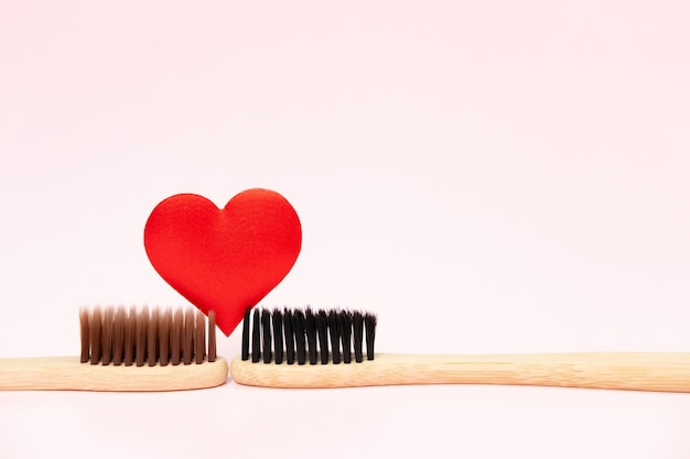 Duas escovas de dente de bambu com coração vermelho em fundo rosa