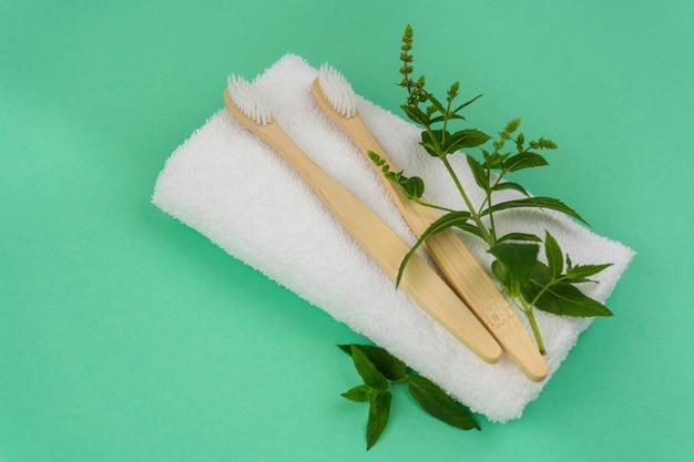 Duas escovas de dente de bambu com raminhos de hortelã e uma toalha branca em um fundo de hortelã