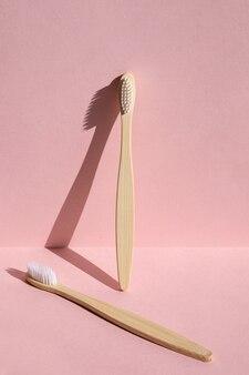 Duas escovas de dente de bambu ecológicas em um fundo rosa luz forte