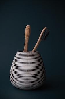 Duas escovas de dente de bambu em um vidro de porcelana em um fundo gradiente de ciano