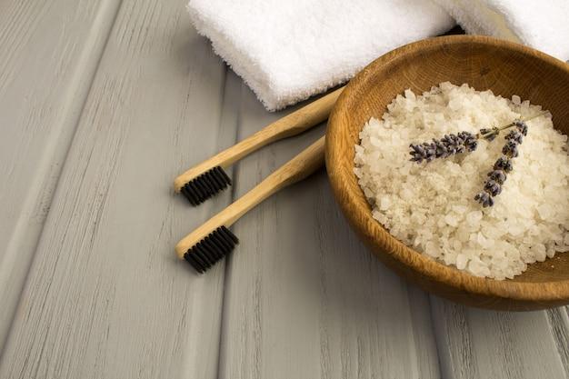 Duas escovas de dente de bambu, toalha branca e sal de banho marinho na tigela marrom sobre o fundo cinza de madeira