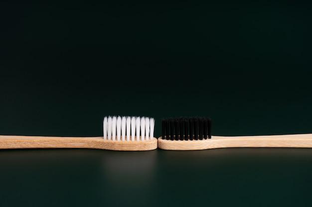 Duas escovas de dente de madeira de bambu antibacterianas ecológicas com cerdas brancas e pretas em um fundo preto. cuidar do meio ambiente é tendência. tolerância. copie o espaço.