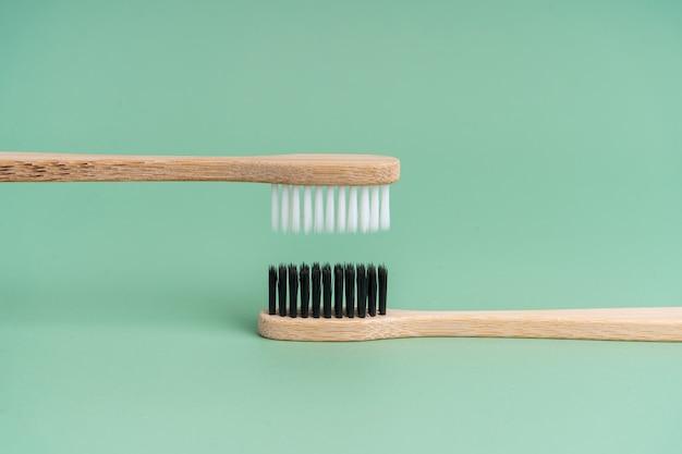 Duas escovas de dente de madeira de bambu antibacterianas ecológicas com cerdas brancas e pretas sobre um fundo verde claro. cuidar do meio ambiente é tendência. tolerância. copie o espaço.