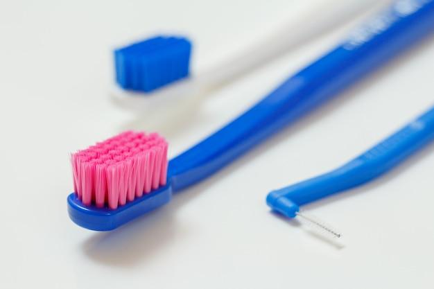 Duas escovas de dente e uma escova interdental em fundo branco. profundidade superficial de campo.