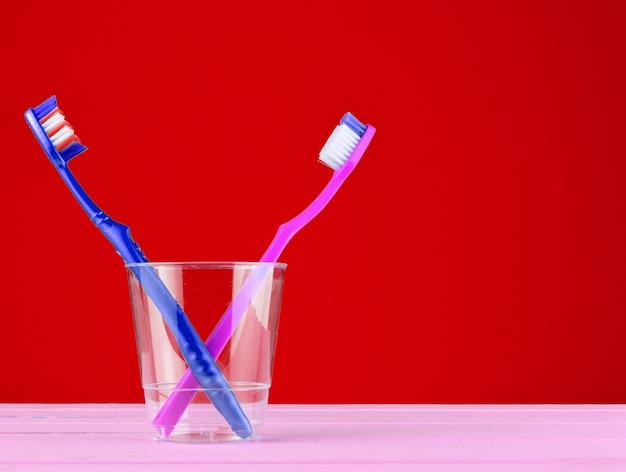 Duas escovas de dente em um copo de plástico transparente no banheiro