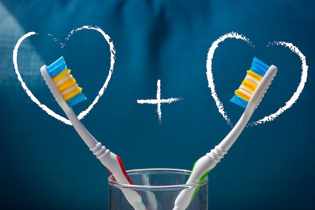 Duas escovas de dente em um fundo azul e dois corações com um sinal de adição. amor e dia dos namorados. copie o espaço