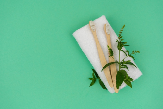 Duas escovas de dente feitas de material ecológico com um raminho de hortelã verde e uma toalha branca em um fundo de hortelã