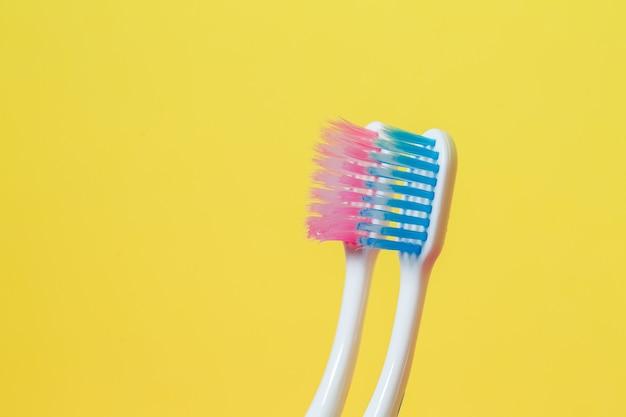 Duas escovas de dente rosa e azul. conceito de escova de dentes para um casal que vive junto como o início de uma família Foto Premium