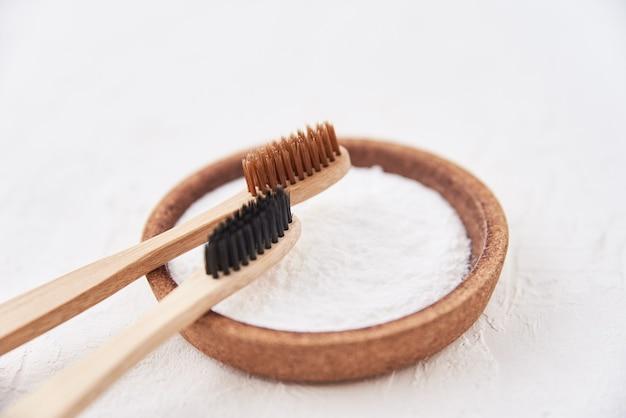 Duas escovas de dentes de bambu de madeira e bicarbonato de sódio em um branco.