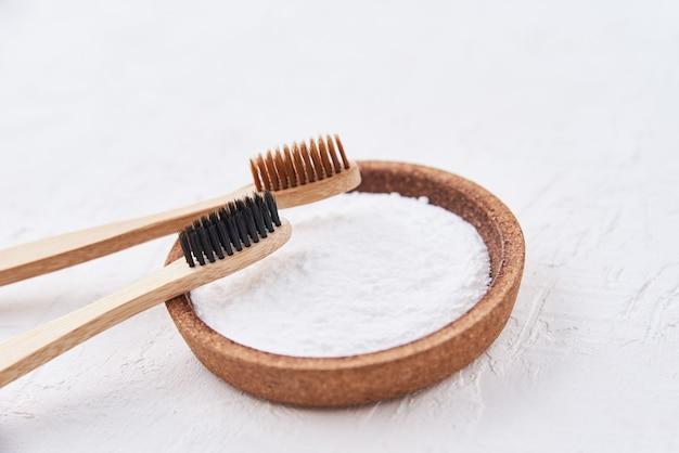 Duas escovas de dentes de bambu de madeira e bicarbonato de sódio em um fundo branco. escovas de dentes ecológicas, conceito de desperdício zero